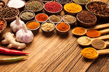 A selection of various colorful spices on a wooden table in bowls Archivio Fotografico