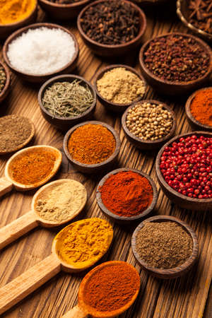 A selection of various colorful spices on a wooden table in bowls Фото со стока - 24434416