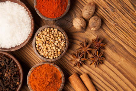curry powder: A selection of various colorful spices on a wooden table in bowls Stock Photo