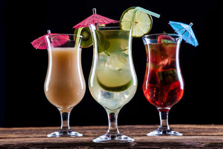 Fresh tasty drinks on black background with fruits photo