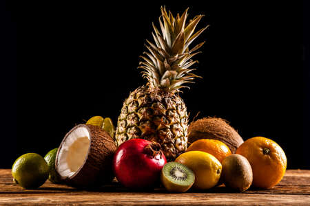 Tasty fruits on wooden table, on black background photo