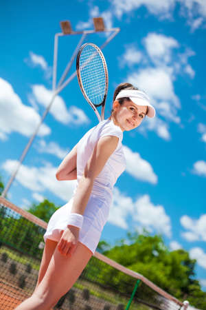 Female playing tennis on court photo