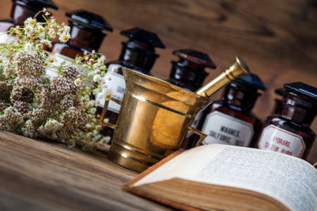 The ancient natural medicine, herbs,  medicines and old book photo