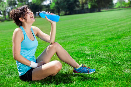 Tired woman runner taking a rest after run, drinking water photo