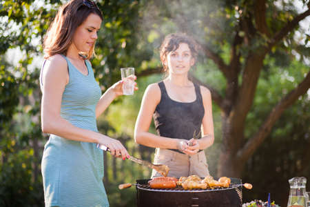 garden barbecue: Two pretty girls making food on grill