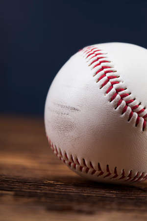Baseball ball on wooden table and blue backgdound photo