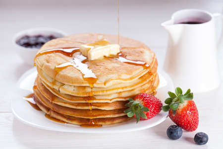 Delicious sweet American pancakes on a plate with fresh fruits and addons. photo