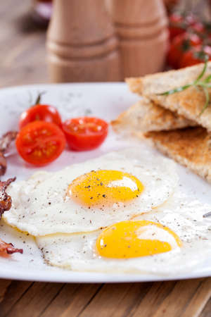 Fried egg and bacon on a plate with spices and vegetables. Studio shot photo