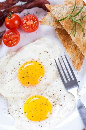 huevos fritos: Huevo frito y tocino en un plato con especias y verduras. Tiro del estudio