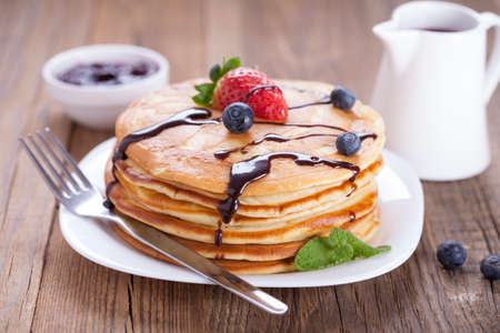 Delicious sweet American pancakes on a white plate with fresh fruits, sauce and side dishes. photo