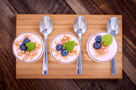 Delicious dessert, flakes flooded in two flavors yogurt with blueberries and fruit on a wooden board.  photo
