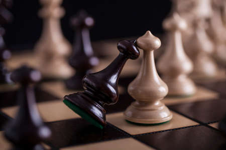 chess: Ajedrez. peones blancos vs negro sobre tablero de madera