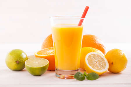 Healthy and fresh mixed juice from fruits on white wooden table