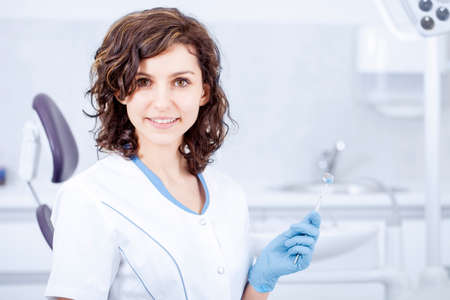 Young professional woman dentist in the office on the background of the chair and dental accessories