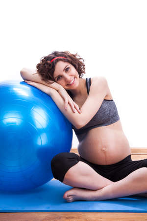 Young pregnant woman exercises with the ball. photo