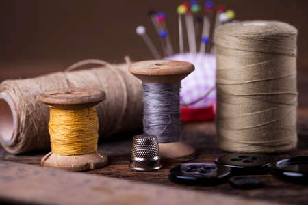 Sewing instruments, threads, needles, bobbins and materials. Studio photo