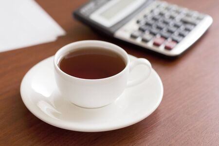 workplace with a cup of coffee, a calculator and paper. Close-up image photo
