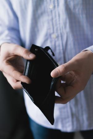empty wallet: Man holding an empty wallet