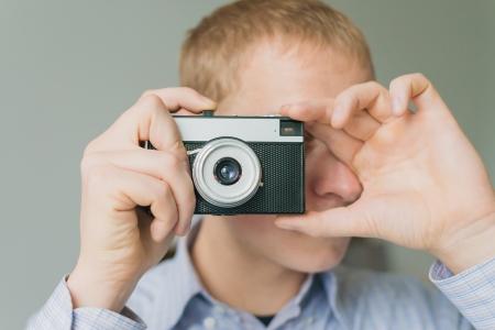 Man photographs on film camera photo