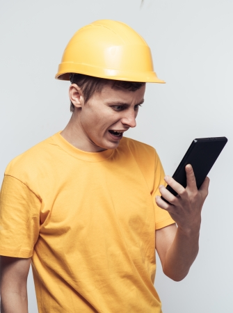 Man worker in a helmet stares at tablet pc photo