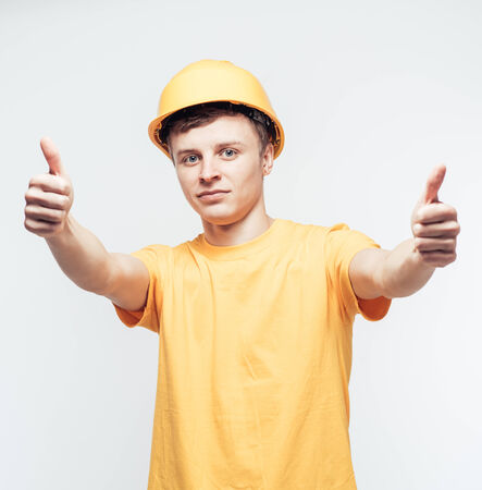 Worker in yellow helmet holding thumb up