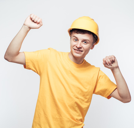Worker in yellow helmet with joyful hands raised photo