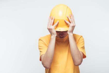 reflective background: Worker in yellow helmet upset
