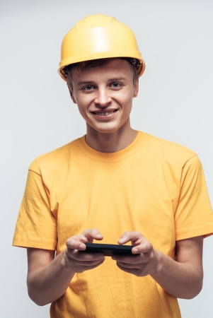 Worker in yellow helmet plays in the phone