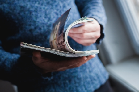 persona leyendo: Un hombre mira una revista. Presione manos.