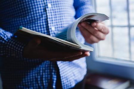 Un uomo guarda una rivista. Premere mani.