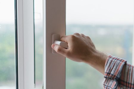 Male hand opens a window