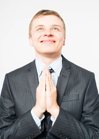 young businessman praying with his hands set in pray photo