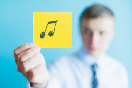 melodious: man holding a musical note