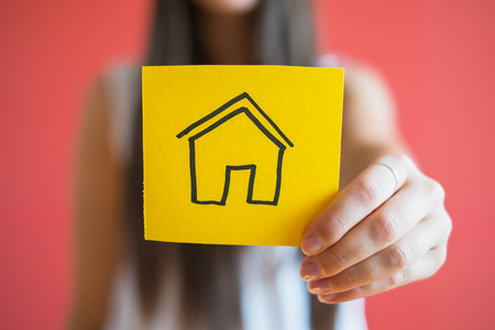 hands holding house: drawing paper house icon in the hand Stock Photo