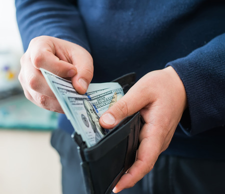 cash on hand: Purse with dollars in their hands. Stock Photo