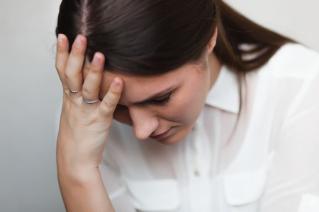 Beautiful and sad young woman. Headache or problems, hand at her forehead. photo