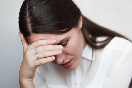 Beautiful and sad young woman. Headache or problems, hand at her forehead.