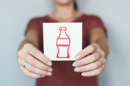 carbonated: Picture icon in the hands of drink in a bottle