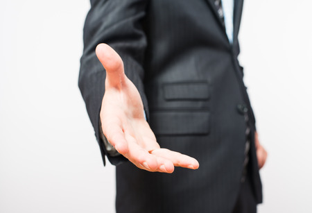 stretched: Close-up of a businessmans hand, held out for a handshake. Isolated on white with a clipping path included. Businessman dressed in a pinstripe suit, a little of which can be seen.