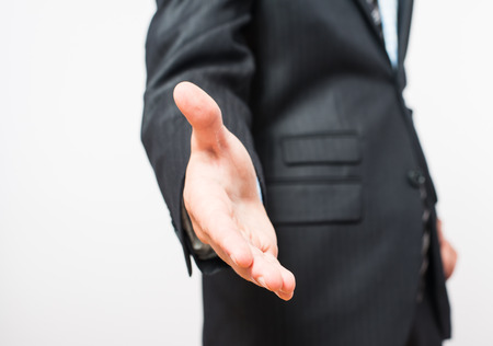 greets: Close-up of a businessmans hand, held out for a handshake. Isolated on white with a clipping path included. Businessman dressed in a pinstripe suit, a little of which can be seen.