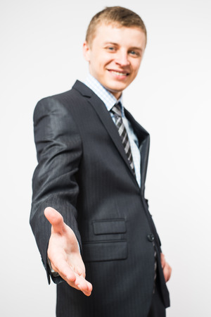 be dressed in: Close-up of a businessmans hand, held out for a handshake. Isolated on white with a clipping path included. Businessman dressed in a pinstripe suit, a little of which can be seen.