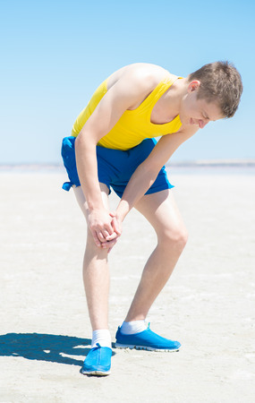 excruciating: Male athlete on floor clutching knee and hamstring in excruciating pain on white background Stock Photo