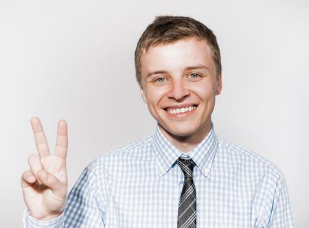 simbolo de la paz: Retrato de un hombre de negocios que muestra signo de la victoria