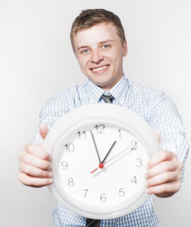 anguished: Discontented  businessman holding wall clock.