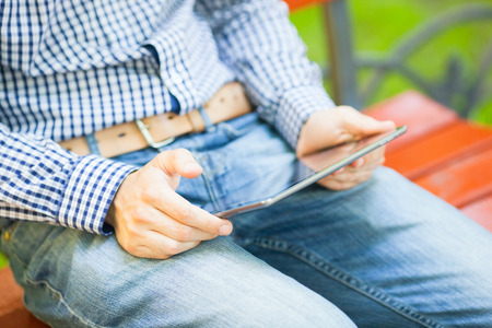 freaks: The man uses a digital tablet in park Stock Photo