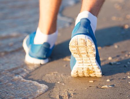 Athlete running in the sand feet