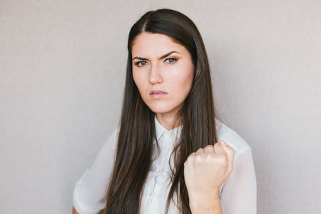 malice: Half-length portrait of beautiful dark-haired young angry woman wearing white blouse   showing us her fists Stock Photo