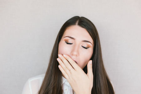 young brunette woman yawns
