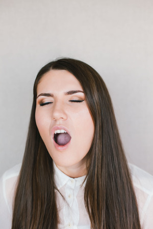 mouth close up: young brunette woman yawns