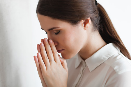 woman praying: Closeup portrait of a young woman praying